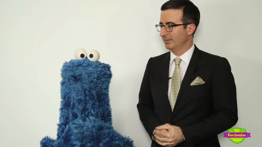 Cookie Monster and John Oliver on screen in the skit from Sesame Street.